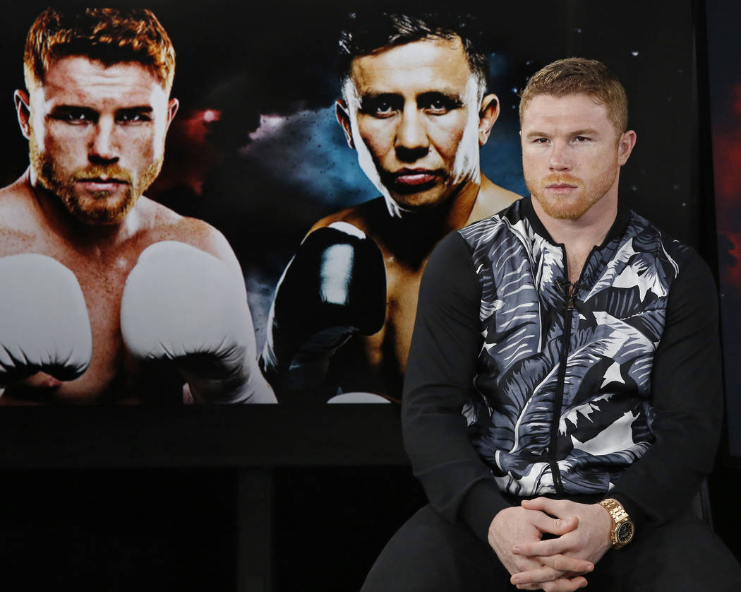 "Six-time boxing title holder Saul ""Canelo"" Alvarez, of Mexico, right, sits beside giant photographic portraits of himself, left, and his upcoming opponent, IBF and WBC world midd ..."