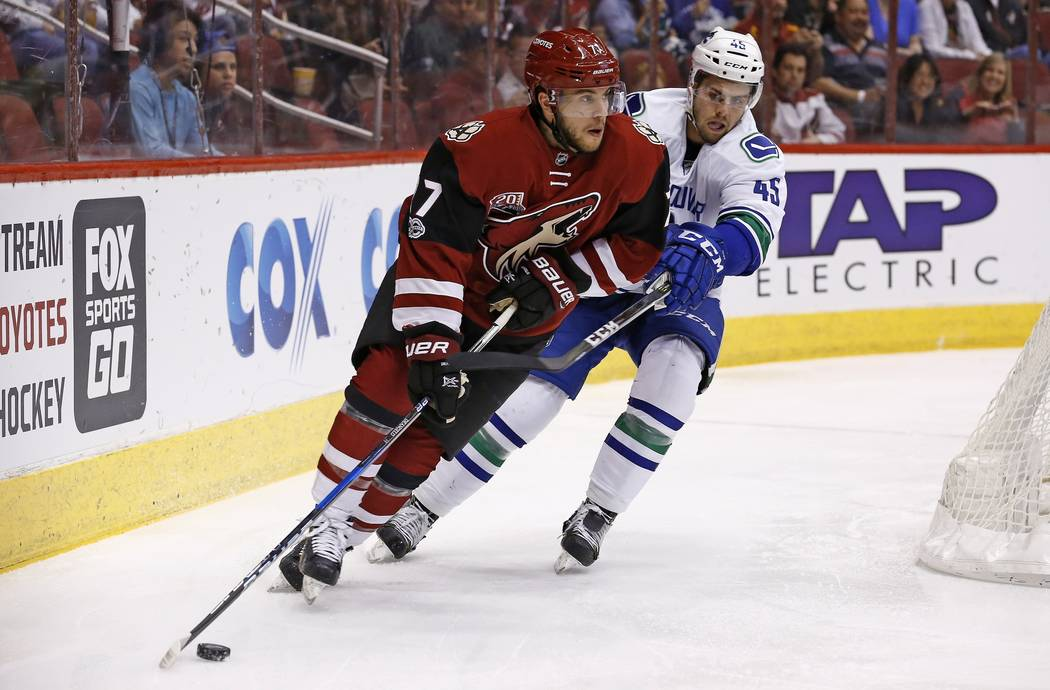 Arizona Coyotes' Anthony DeAngelo, left, skates with the puck in front of Vancouver Canucks' Michael Chaput (45) during the first period of an NHL hockey game Thursday, April 6, 2017, in Glendale, ...