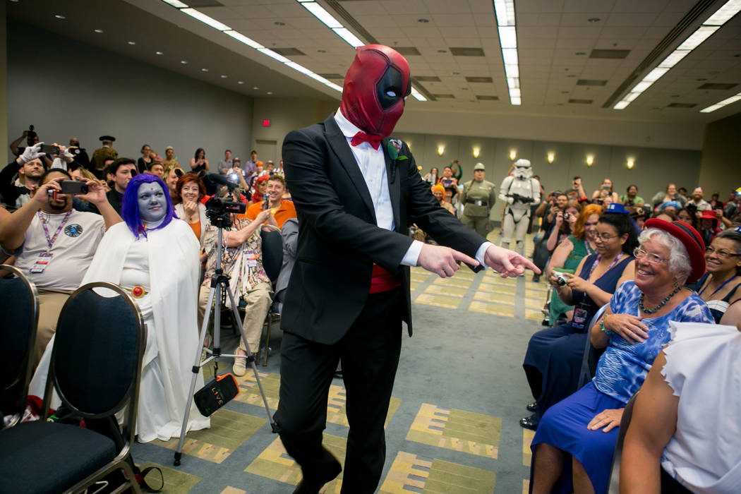 Groom Adam Merica, dressed as Deadpool, makes his way down the aisle to marry his bride at AwesomeCon in Washington, DC on June 17, 2017. (Linda Wang/The Washington Post)