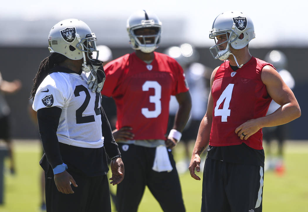 Oakland Raiders running back Marshawn Lynch (24), quarterback EJ Manuel (3) and quarterback Derek Carr (4) talk during day two of a mini-camp at the Raiders headquarters and training facility in A ...