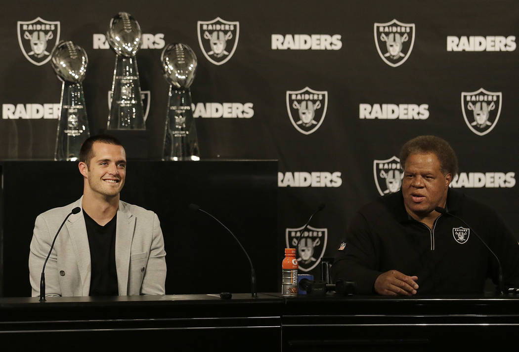Oakland Raiders quarterback Derek Carr, left, listens as general manager Reggie McKenzie speaks at a news conference in Oakland, Calif., Friday, June 23, 2017. Carr finalized a five-year contract  ...