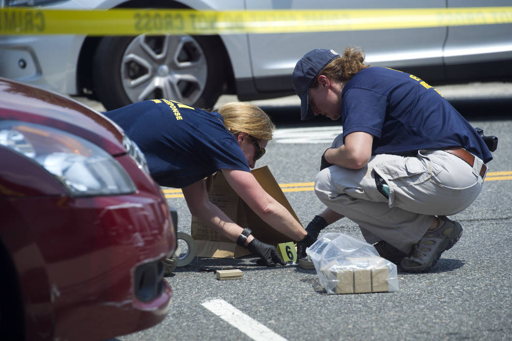 FBI Evidence Response Team members mark evidence at the scene of a multiple shooting in Alexandria, Va., Wednesday, June 14, 2017, involving House Majority Whip Steve Scalise of La., and others du ...