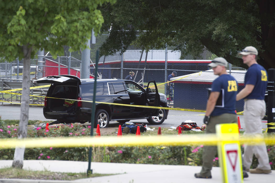 An SUV, with a bullet hole in the windshield and a flat tire, sits in the parking lot at the scene of a multiple shooting in Alexandria, Va., Wednesday, June 14, 2017, involving House Majority Whi ...