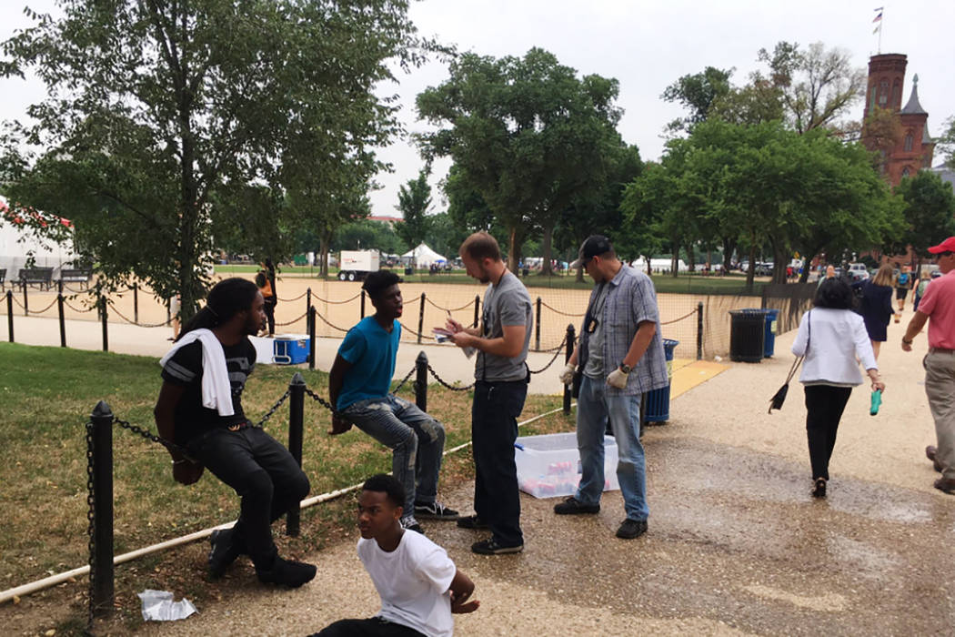 Plainclothes officers cuff three teenagers who were selling water on the National Mall in Washington, D.C. on Friday, June 23, 2017. (@timkrepp/Twitter)