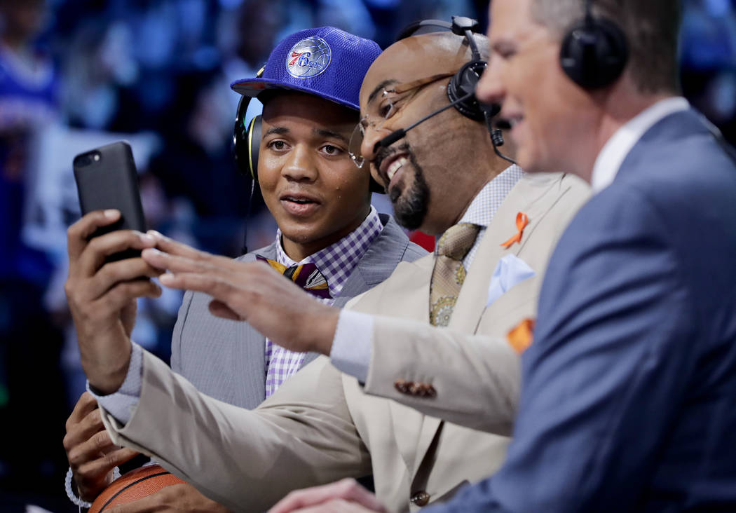 Washington's Markelle Fultz smiles for a selfie with a television commentator after being selected by the Philadelphia 76ers as the No. 1 pick overall during the NBA basketball draft, Thursday, Ju ...