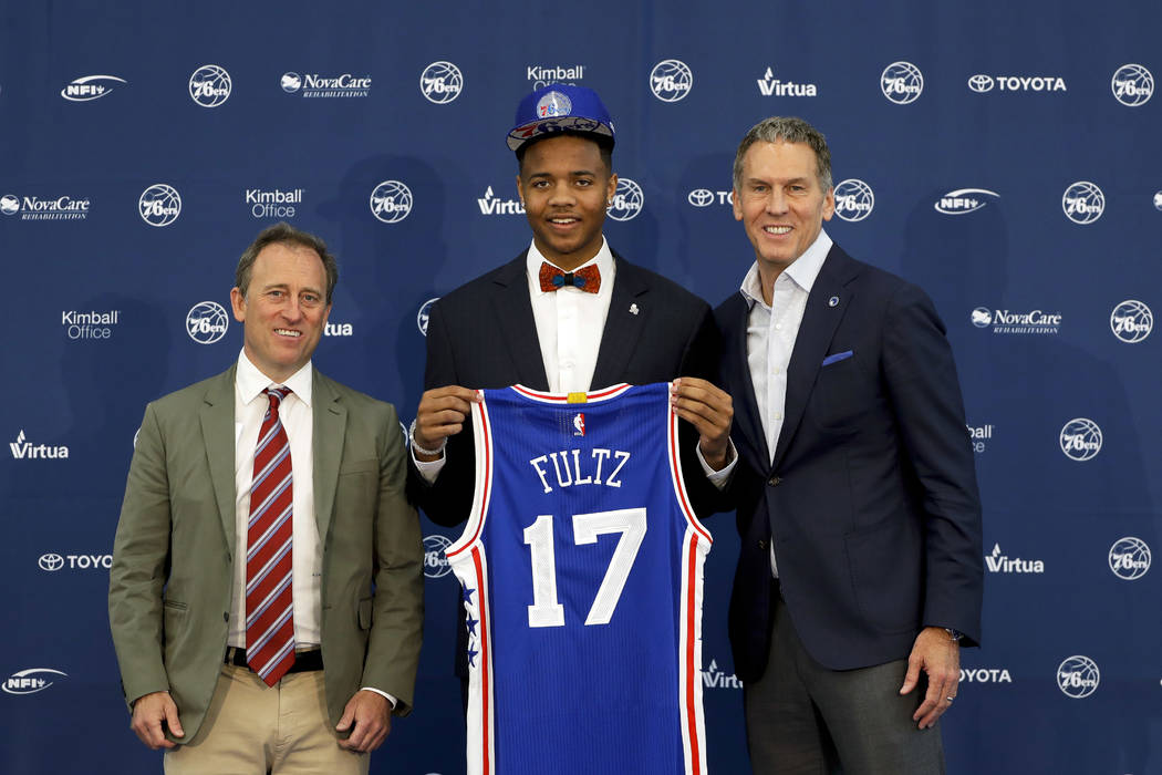 Philadelphia 76ers' draft pick Markelle Fultz, center, poses with team president Bryan Colangelo, right, and managing owner Josh Harris after a news conference at the team's NBA basketball trainin ...