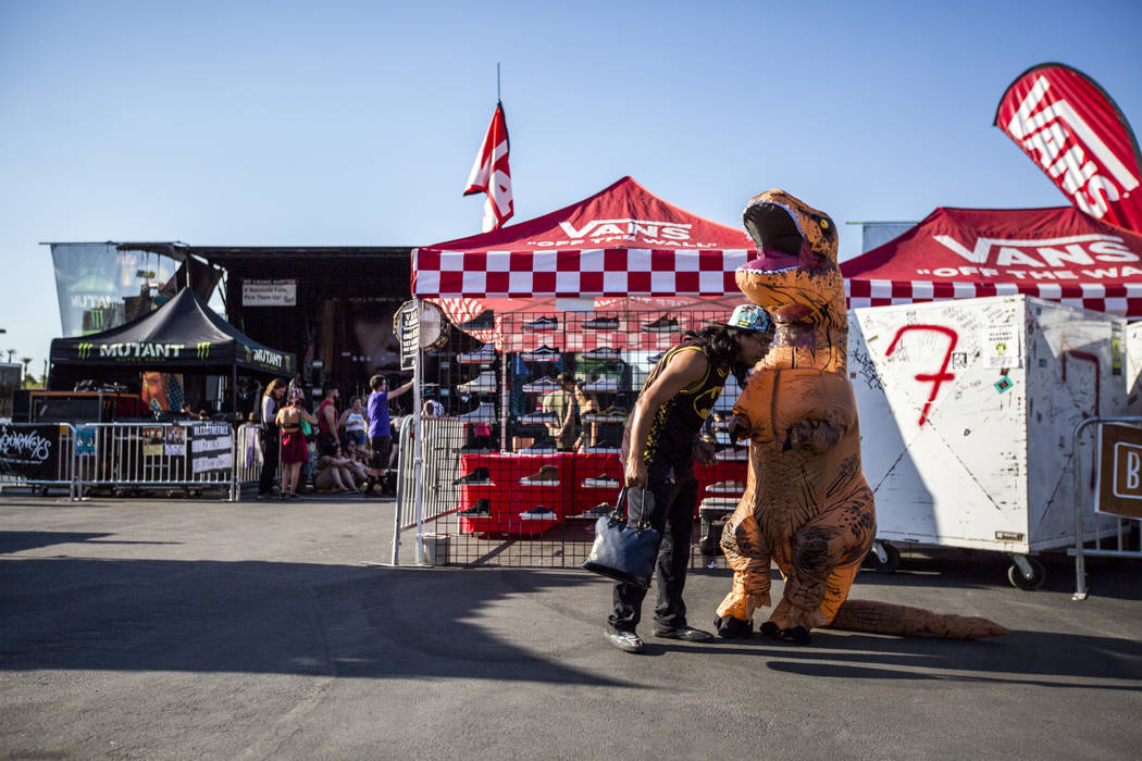 Larry Sanroman checks on his friend Jennifer Paddock in her dinosaur costume at Vans Warped Tour at the Hard Rock Hotel and Casino on Friday, June 23, 2017.  Patrick Connolly Las Vegas Review-Jour ...