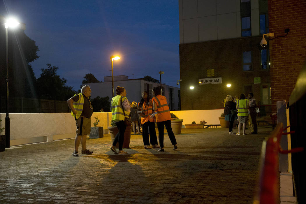 Camden council representatives talk as they help residents as they are evacuated from the Burnham residential tower block on the Chalcots Estate, in the borough of Camden, north London, Friday, Ju ...