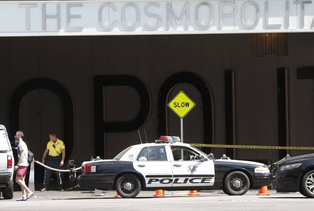 A police officer stands guard outside The Cosmopolitan hotel-casino where Las Vegas police are attempting to contact a man who barricaded himself in a stolen car at the parking garage Las Vegas on ...