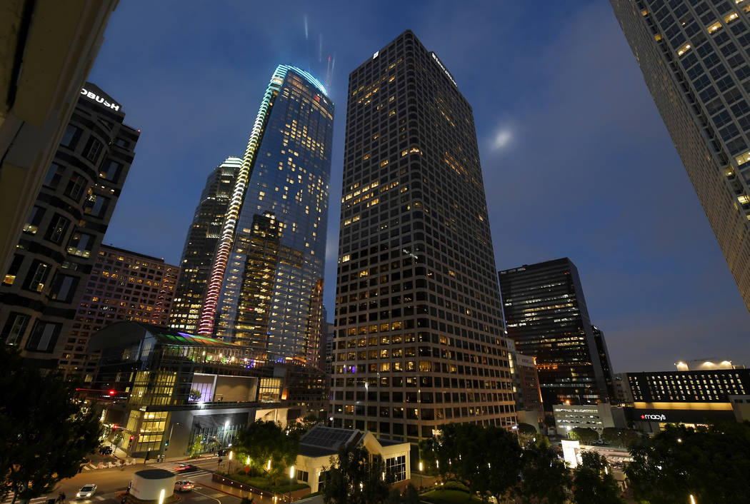 A light show illuminates Wilshire Grand Center, center left, to celebrate its grand opening, Friday, June 23, 2017, in Los Angeles. The 73-story, 1,100-foot-high structure is the tallest building  ...