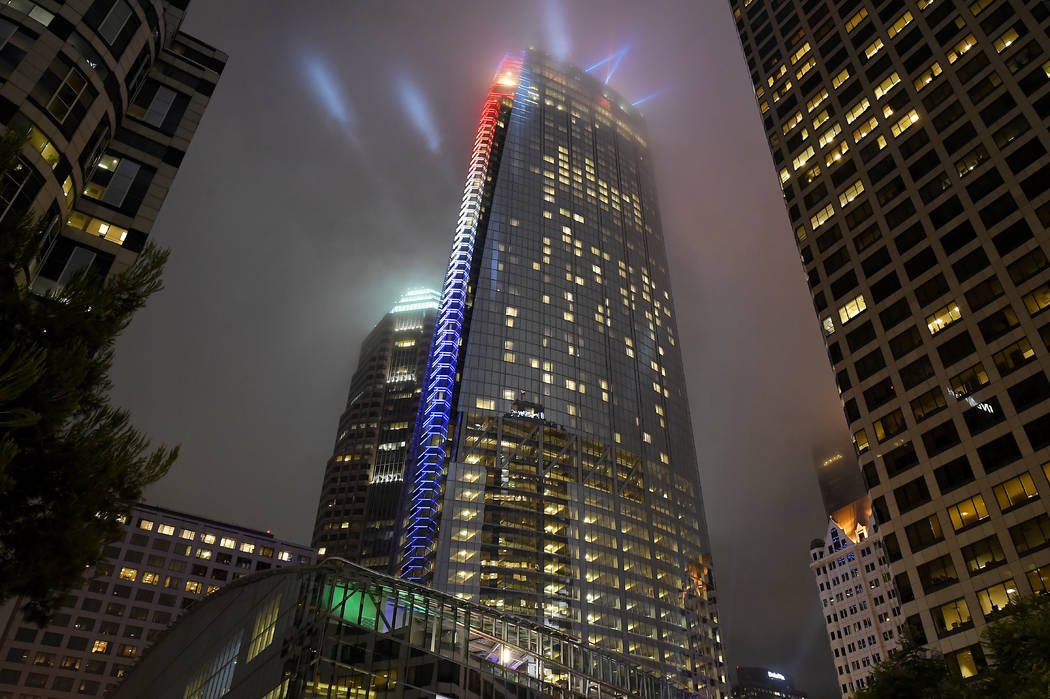 A light show illuminates Wilshire Grand Center to celebrate its grand opening, Friday, June 23, 2017, in Los Angeles. The 73-story, 1,100-foot-high structure is the tallest building west of the Mi ...