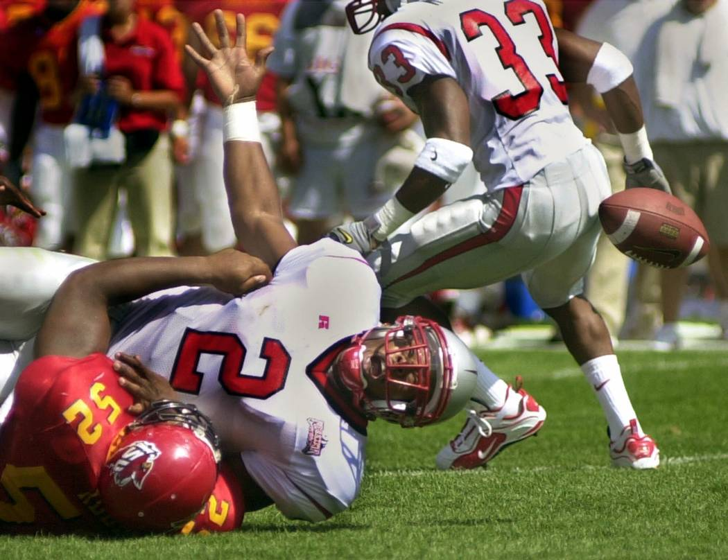 UNLV quarterback Jason Thomas (2) watches the ball bounce away after a tackle by Iowa State's James Reed in the first half Saturday, Sept. 9, 2000, in Ames, Iowa. (AP Photo/Steve Pope)