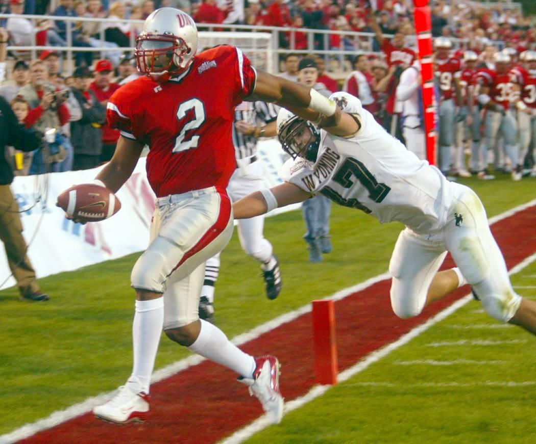 UNLV quarterback Jason Thomas (2) slips past Wyoming linebacker Tyler Gottschalk for the second of his three first-quarter rushing touchdowns Saturday, Nov 2, 2002, at Sam Boyd Stadium in Las Vega ...
