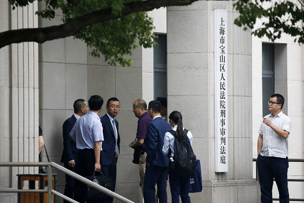 Lawyers chat outside the Baoshan District People's Court in Shanghai, China, Monday, June 26, 2017. (AP Photo/Andy Wong)