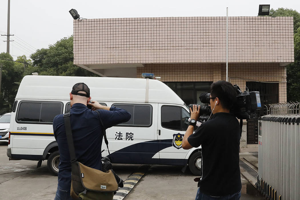 Cameraman and photographer film a court van arrives at an entrance gate of the Baoshan District People's Court in Shanghai, China, Monday, June 26, 2017. (AP Photo/Andy Wong)