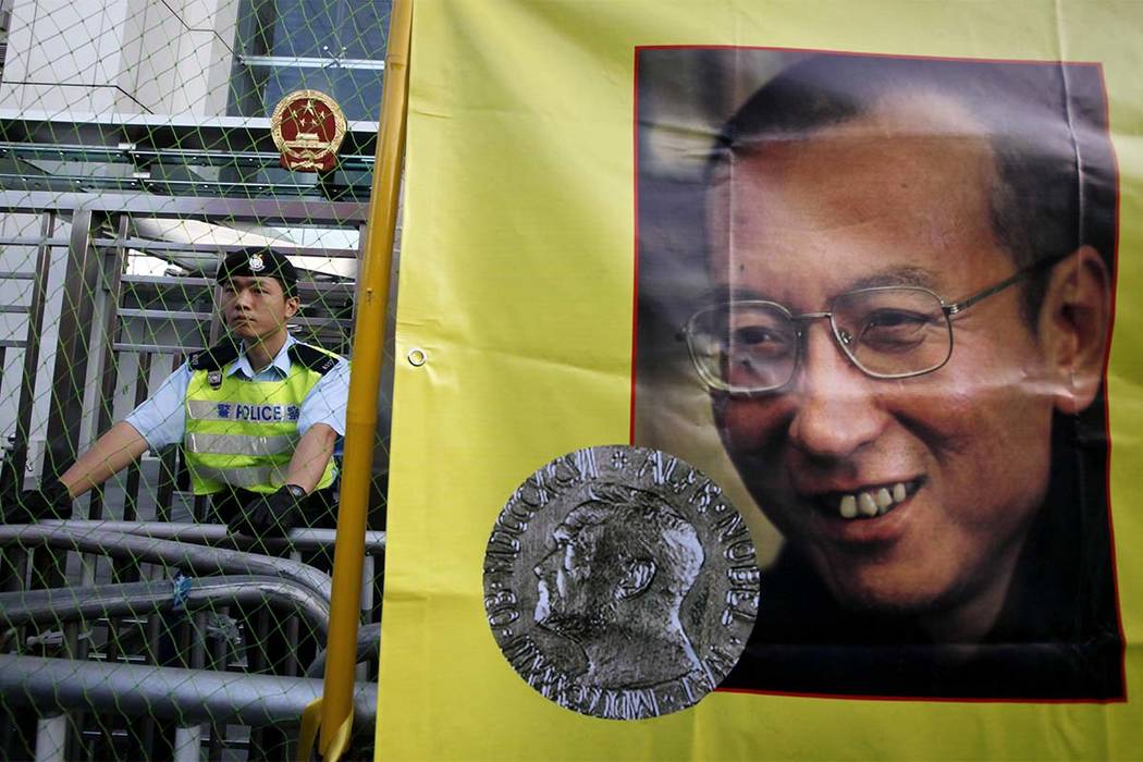 In this Dec. 5, 2010 file photo, a police officer stands guard beside a picture of jailed Chinese dissident Liu Xiaobo outside the Chinese government liaison office in Hong Kong. Jailed Chinese No ...