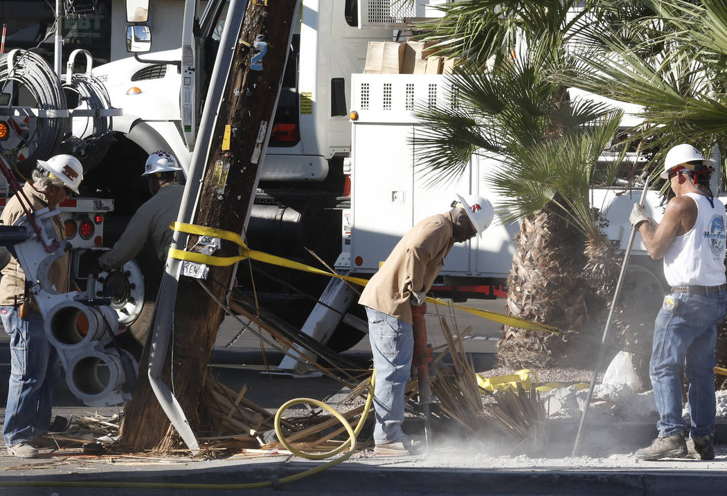 Nevada Energy workers dig out a power pole that was damaged after two vehicles collided and one of the cars crashed into it at East Flamingo Avenue and Mountain Vista on Monday, June 26, 2017. (Bi ...