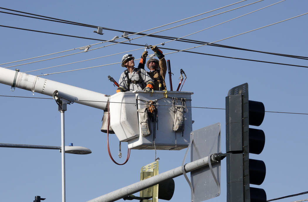 Nevada Energy workers repair a high-voltage power line after two vehicles collided and crashed into a power pole at East Flamingo Avenue and Mountain Vista on Monday, June 26, 2017. (Bizuayehu Tes ...