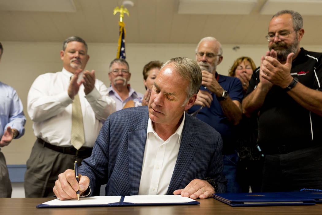 U.S. Secretary of the Interior Ryan Zinke signs a letter authorizing the distribution of federal money to Lincoln County at the Bob Ruud Community Center in Pahrump, Monday, June 26, 2017. Elizabe ...