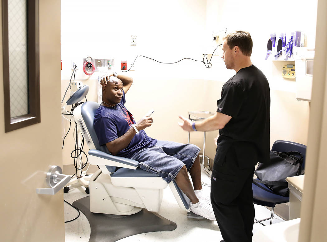 Carlton Davis, left, discusses with Todd Phillips, physician assistant at University Medical Center, about his injury inside UMC's emergency room on Tuesday, June 27, 2017, in Las Vegas. Bizuayehu ...