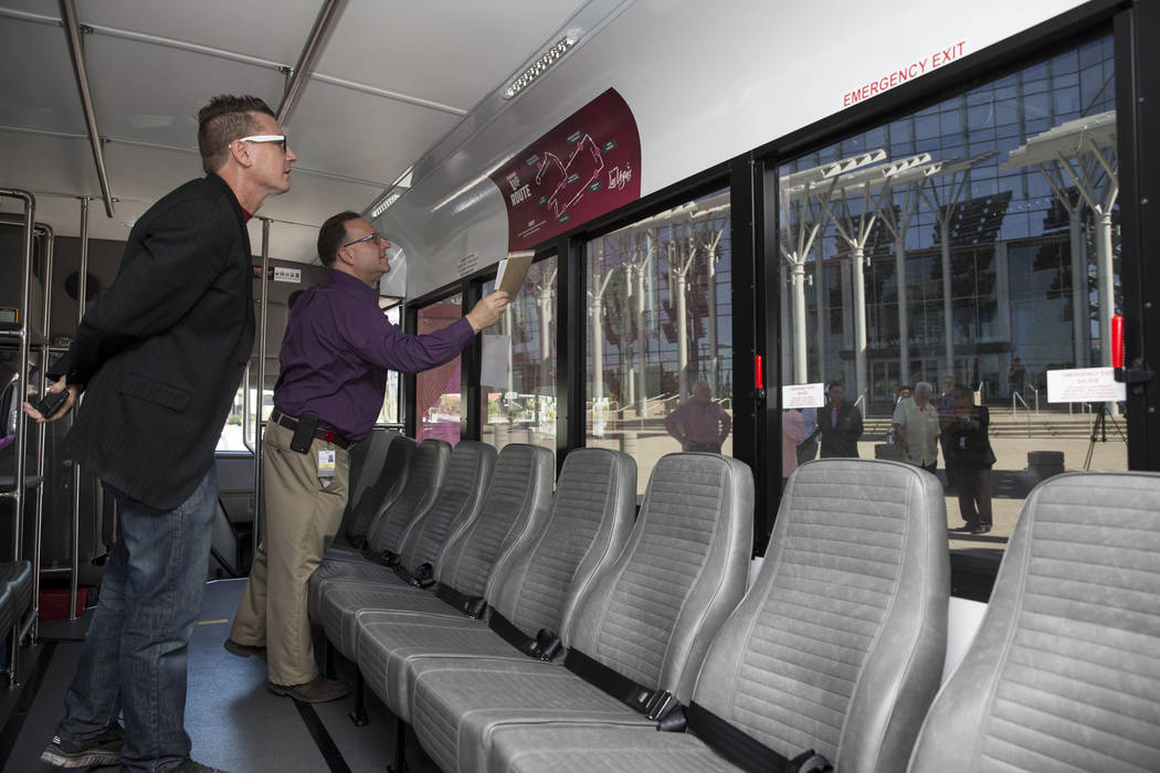Derek Stonebarger, left, Arts District Neighborhood Association board president, and Mark Rosenberg, KCLV Channel 2 station manager, tour the Downtown Loop shuttle bus at Las Vegas City Hall durin ...