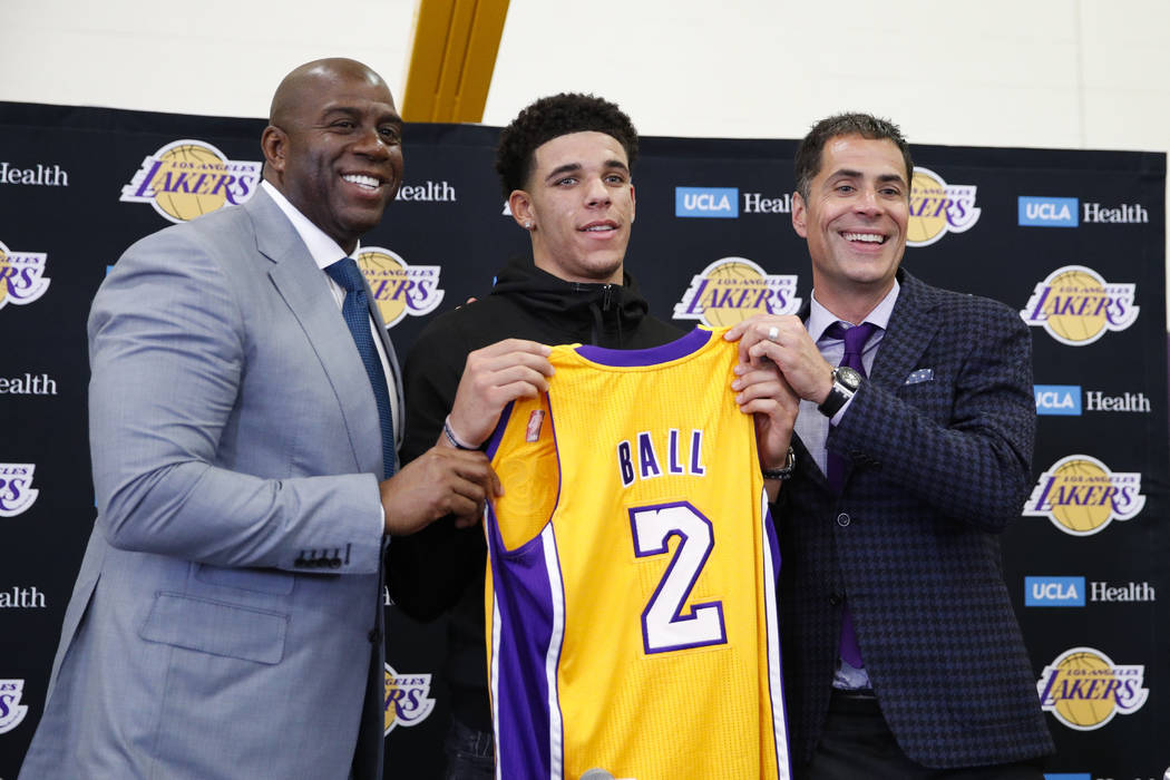Los Angeles Lakers' Lonzo Ball, center, poses for photos with Magic Johnson, left, and general manager Rob Pelinka during a news conference, Friday, June 23, 2017, in El Segundo, Calif. (AP Photo/ ...