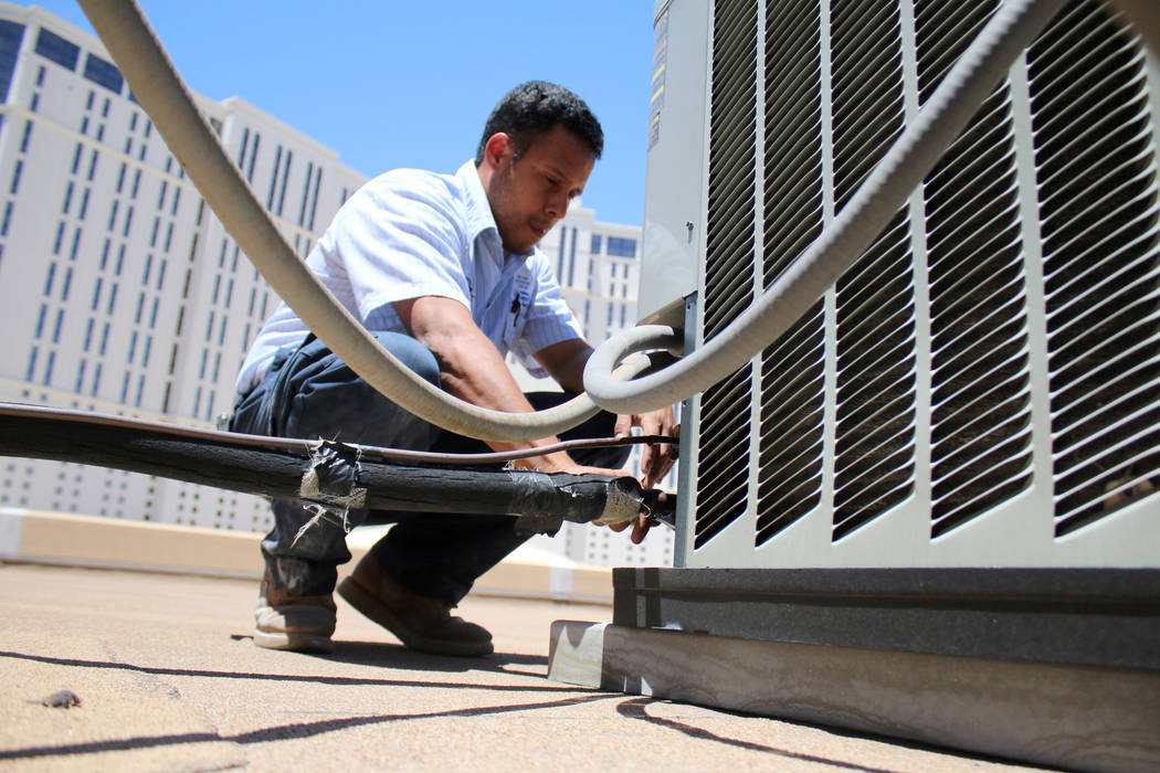 In this July 1, 2014  file photo, air conditioner repairman, Peter Almanza of Cal Air works on an air conditioning unit on the roof of Planet Hollywood Miracle Mile Shops in Las Vegas. (Rachel Cro ...