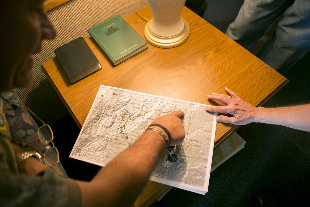 Garfield county sheriff Danny Perkins, left, looks over a map of the Brian Head Fire at the Church of Jesus Christ of Latter-day Saints near Panguitch Lake in Panguitch, Utah which was functioning ...