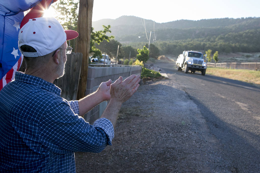 Parowan resident Ted Porray applauds and waves for fire crews as they depart from the Iron Country Fairgrounds on the 11th day of the fire, on Tuesday, June 27, 2017 in Parowan, Utah. Porray retir ...