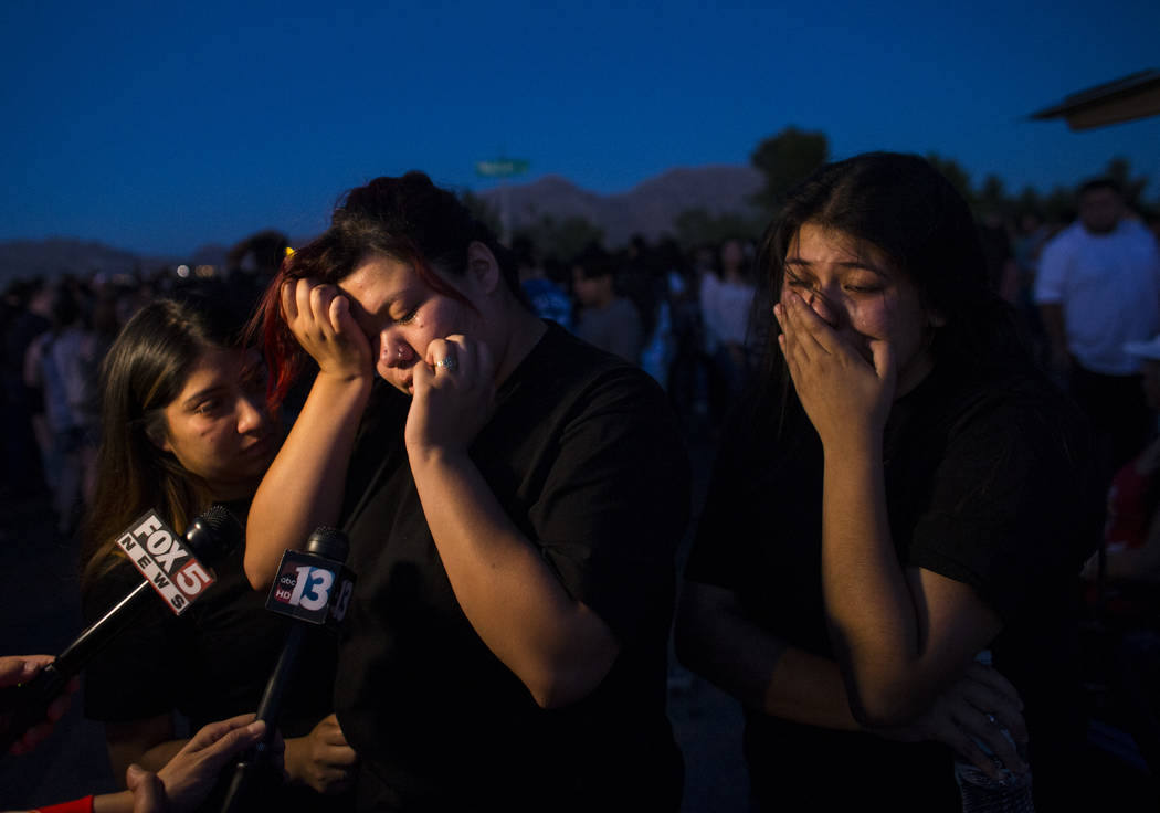 Angelica Reyes, left, reacts during a candlelight vigil for teenagers Oscar Ayala and Moises Rivera, who both died in a crash caused by a drunk driver this past Saturday, at Marion Drive and Judah ...