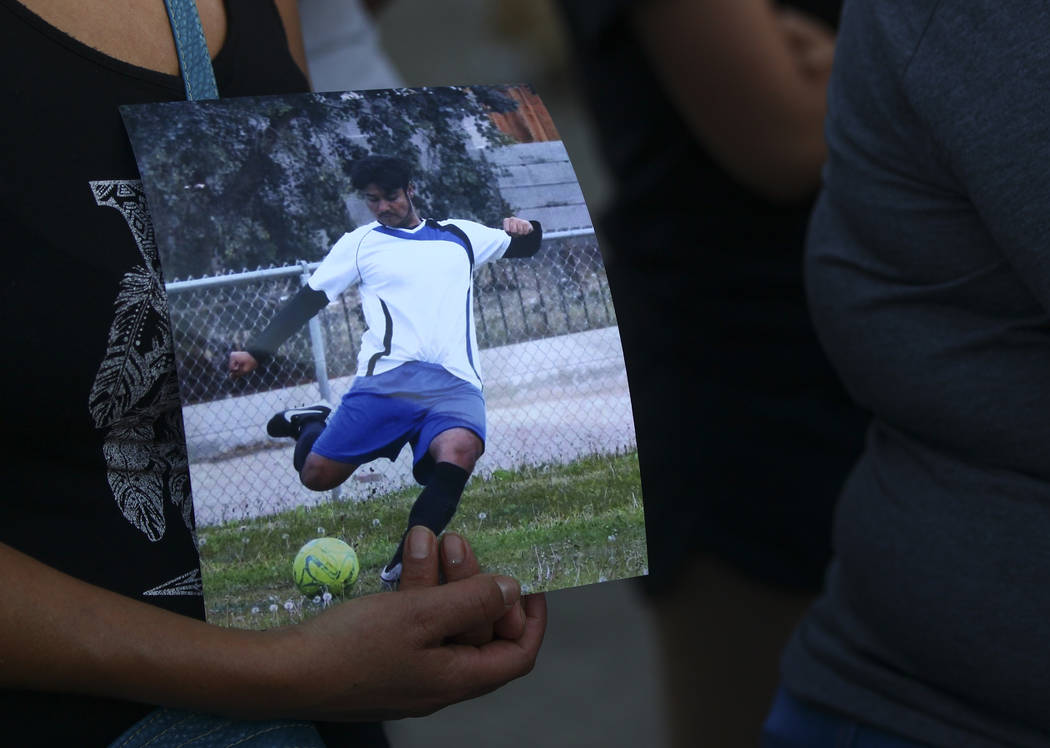 A woman holds a photo of Moises Rivera, 16, one of two teenagers who died in a crash caused by a drunk driver this past Saturday, during a candlelight vigil at Marion Drive and Judah Avenue in Las ...