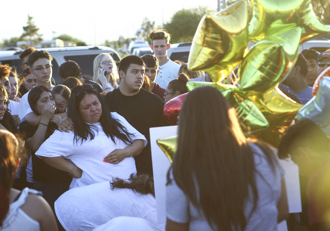 Brenda Covarrubias, center left, whose nephew Oscar Ayala was one of two teenagers killed in a crash caused by a drunk driver this past Saturday, attends a candlelight vigil at Marion Drive and Ju ...