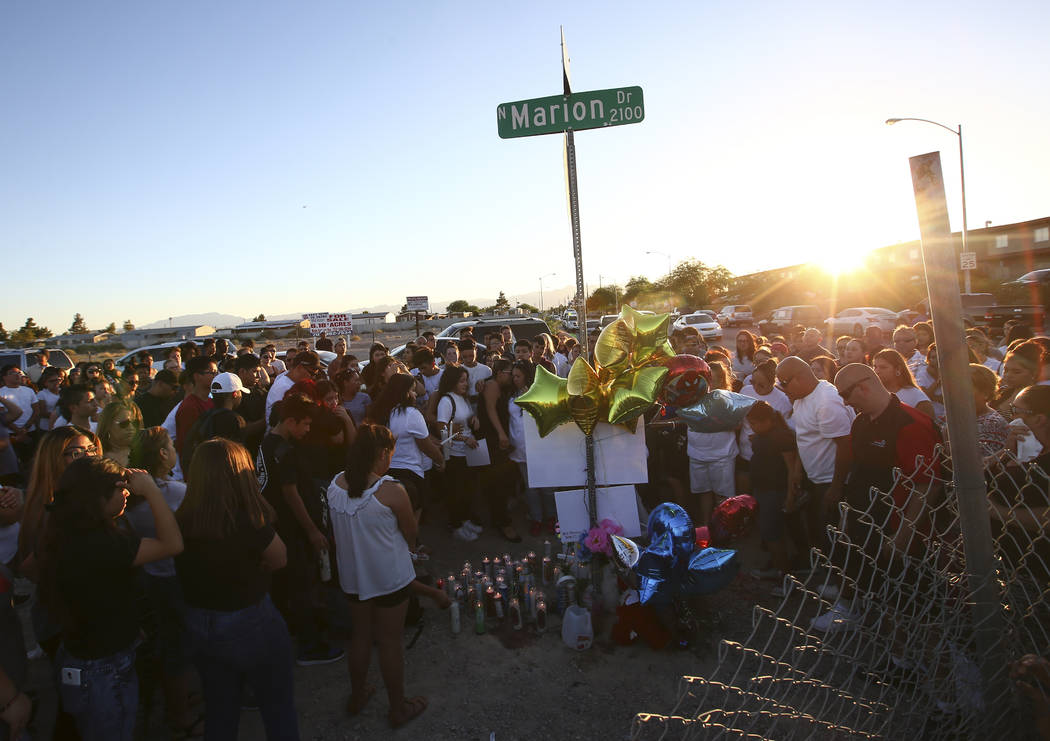 People gather during a candlelight vigil for teenagers Oscar Ayala and Moises Rivera, who both died in a crash caused by a drunk driver this past Saturday, at Marion Drive and Judah Avenue in Las  ...
