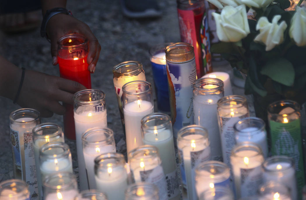 Candles are placed during a candlelight vigil for teenagers Oscar Ayala and Moises Rivera, who both died in a crash caused by a drunk driver this past Saturday, at Marion Drive and Judah Avenue in ...