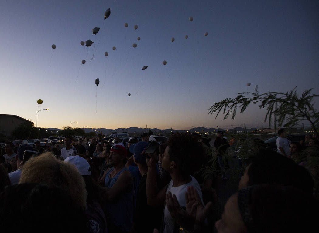 Balloons are released during a candlelight vigil for teenagers Oscar Ayala and Moises Rivera, who both died in a crash caused by a drunk driver this past Saturday, at Marion Drive and Judah Avenue ...