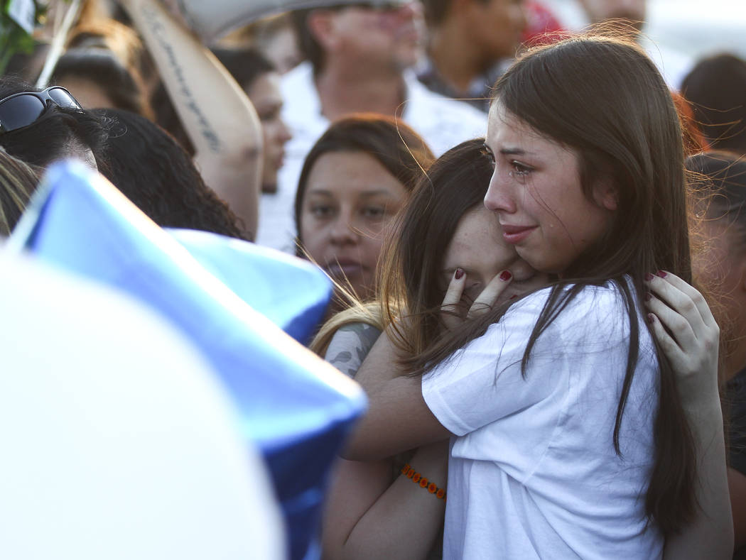 People console one another during a candlelight vigil for teenagers Oscar Ayala and Moises Rivera, who both died in a crash caused by a drunk driver this past Saturday, at Marion Drive and Judah A ...