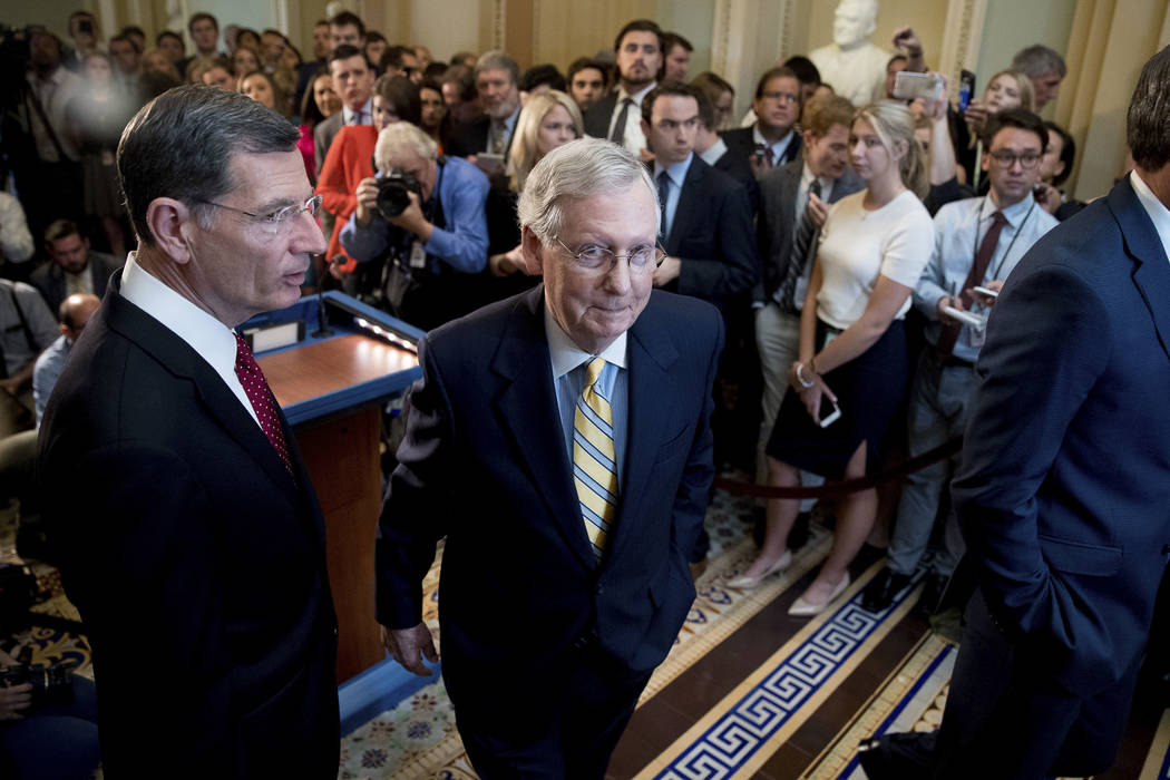 Senate Majority Leader Mitch McConnell, R-Ky., joined by Sen. John Barrasso, R-Wyo., left, departs after announcing that he is delaying a vote on the Republican health care bill while the GOP lead ...