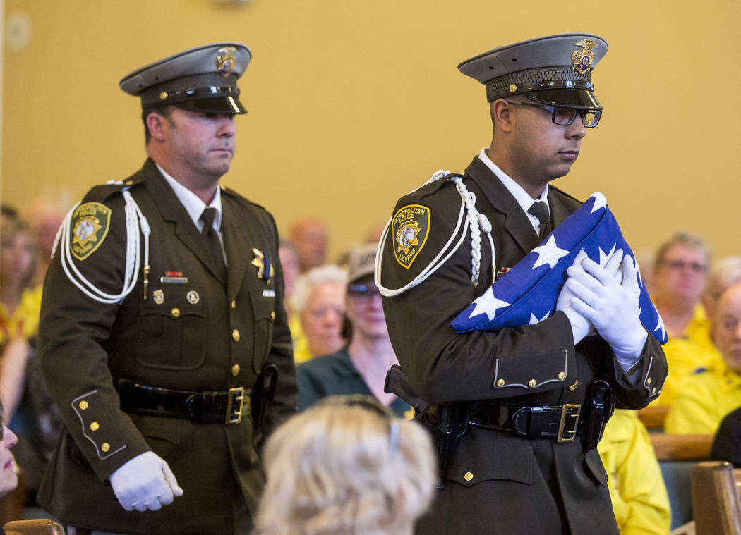 "The Metropolitan Police Honor Guard brings forward the flag during the funeral service for Richard ""Dick"" Bennett, a Metro Police Volunteer with over 20,000 hours of service, at  ..."
