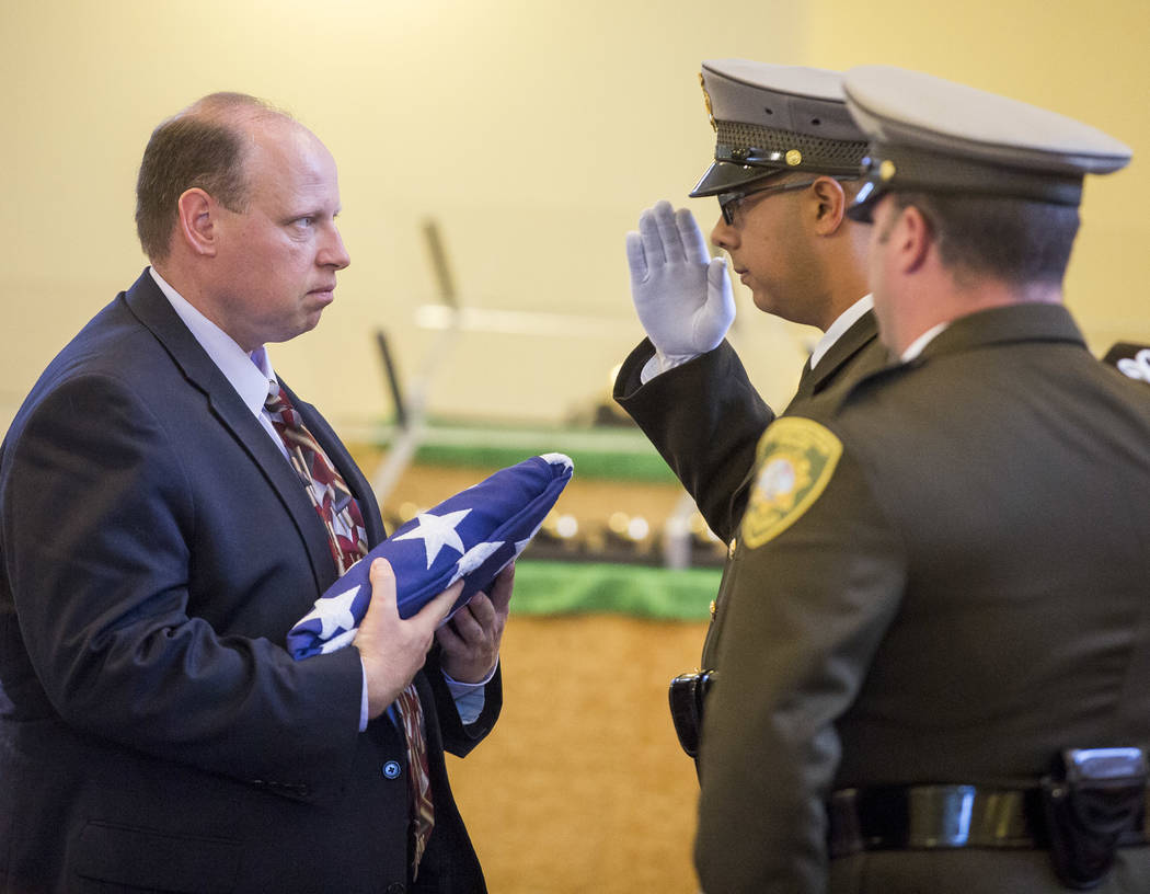 "The Metropolitan Police Honor Guard presents an American flag to Scott Bennett, the son of Richard ""Dick"" Bennett, a Metro Police Volunteer with over 20,000 hours of service, dur ..."