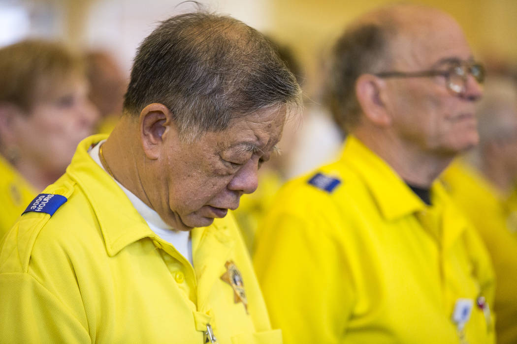 "Robert Lum, a Metropolitan Police Volunteer, bows his head at the funeral service for Richard ""Dick"" Bennett, a Metropo Police Volunteer with over 20,000 hours of service, at the ..."