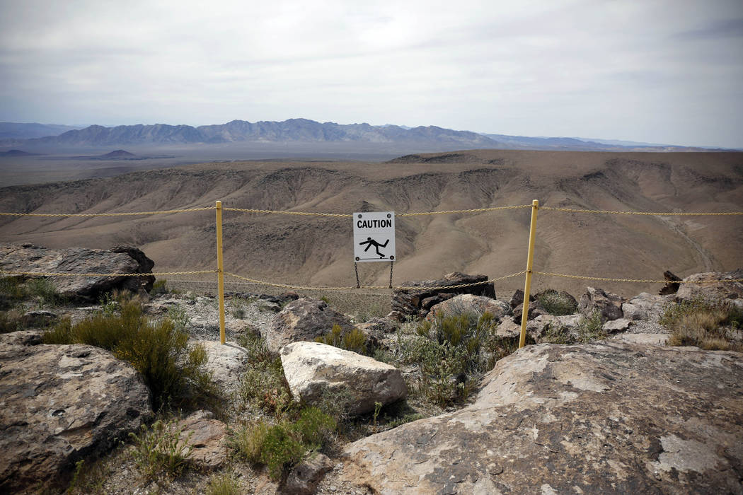 FILE - In this April 9, 2015, file photo, a sign warns of fall danger on the crest of Yucca Mountain during a congressional tour near Mercury, Nev. (AP Photo/John Locher, File)