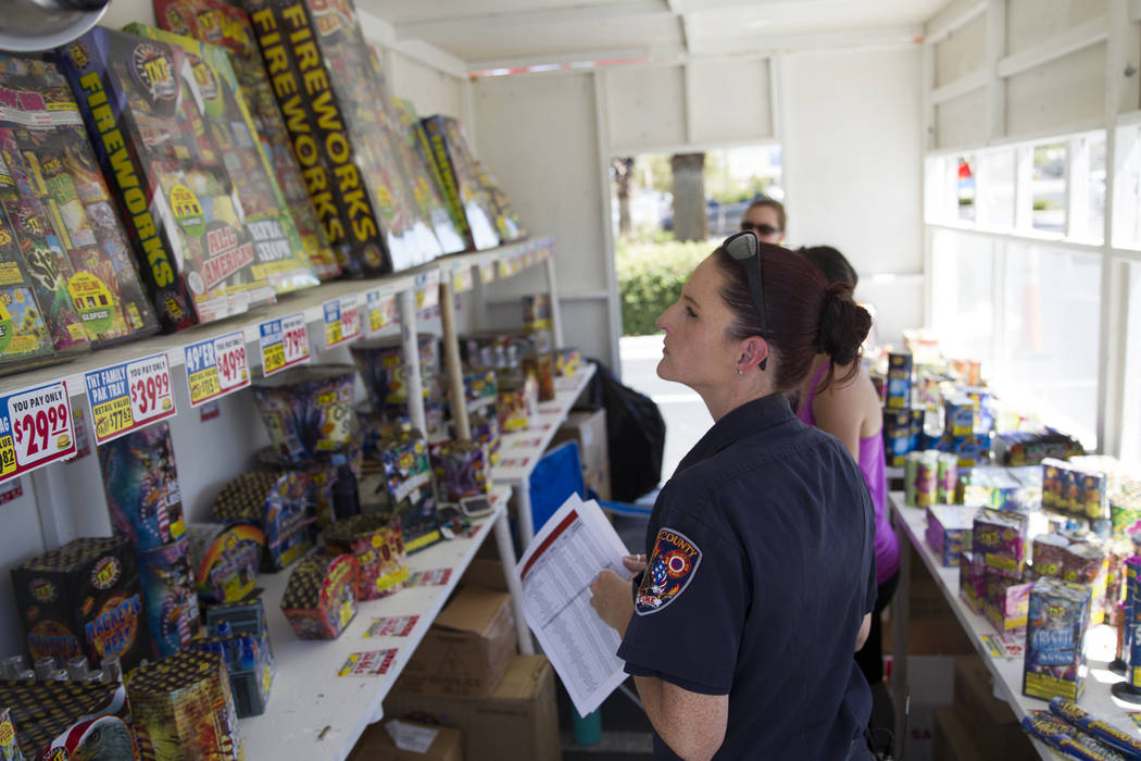Amanda Wildermuth, Clark County fire prevention inspector, inspects a fireworks stand near the intersection of South Rainbow Boulevard and Windmill Lane in Las Vegas, Wednesday, June 28, 2017. (Er ...