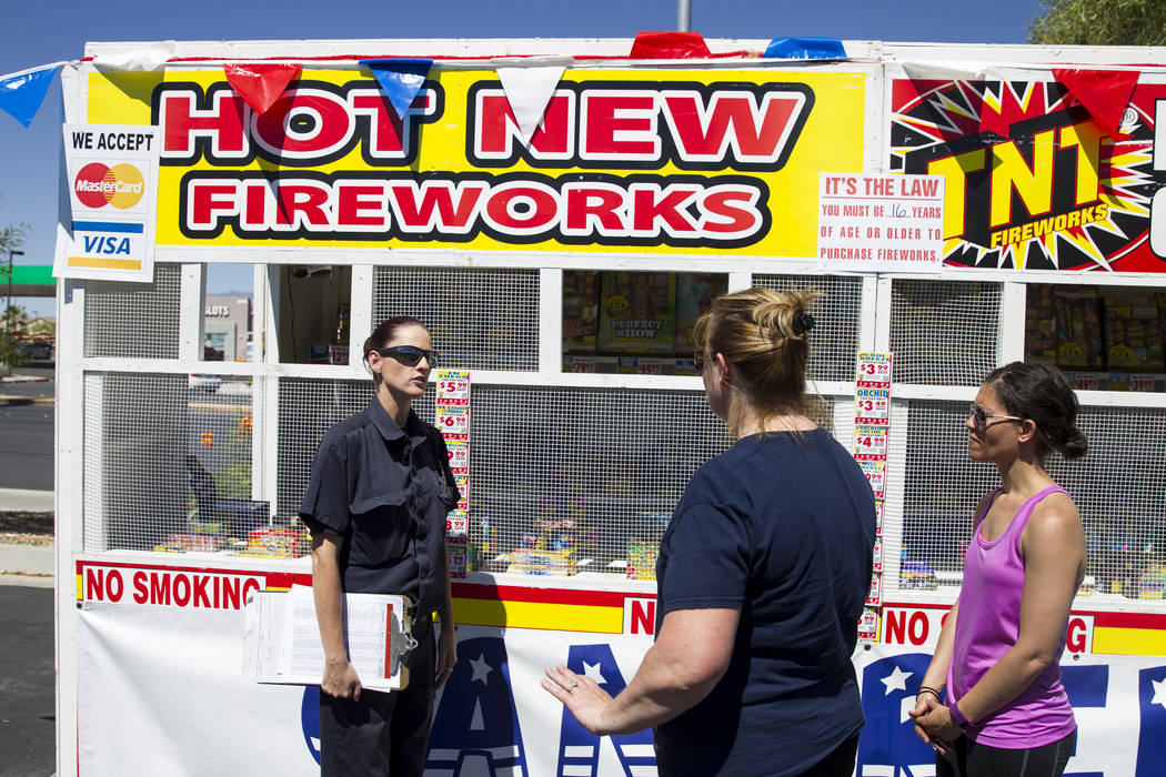 Amanda Wildermuth, left, Clark County fire prevention inspector, inspects a fireworks stand near the intersection of South Rainbow Boulevard and Windmill Lane in Las Vegas, Wednesday, June 28, 201 ...