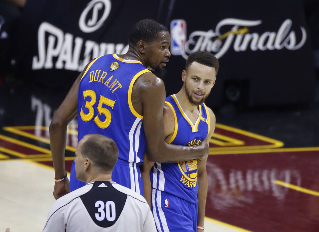 Golden State Warriors forward Kevin Durant (35) holds back Stephen Curry (30) from referee John Goble (30) during the first half against the Cleveland Cavaliers in Game 4 of basketball's NBA Final ...