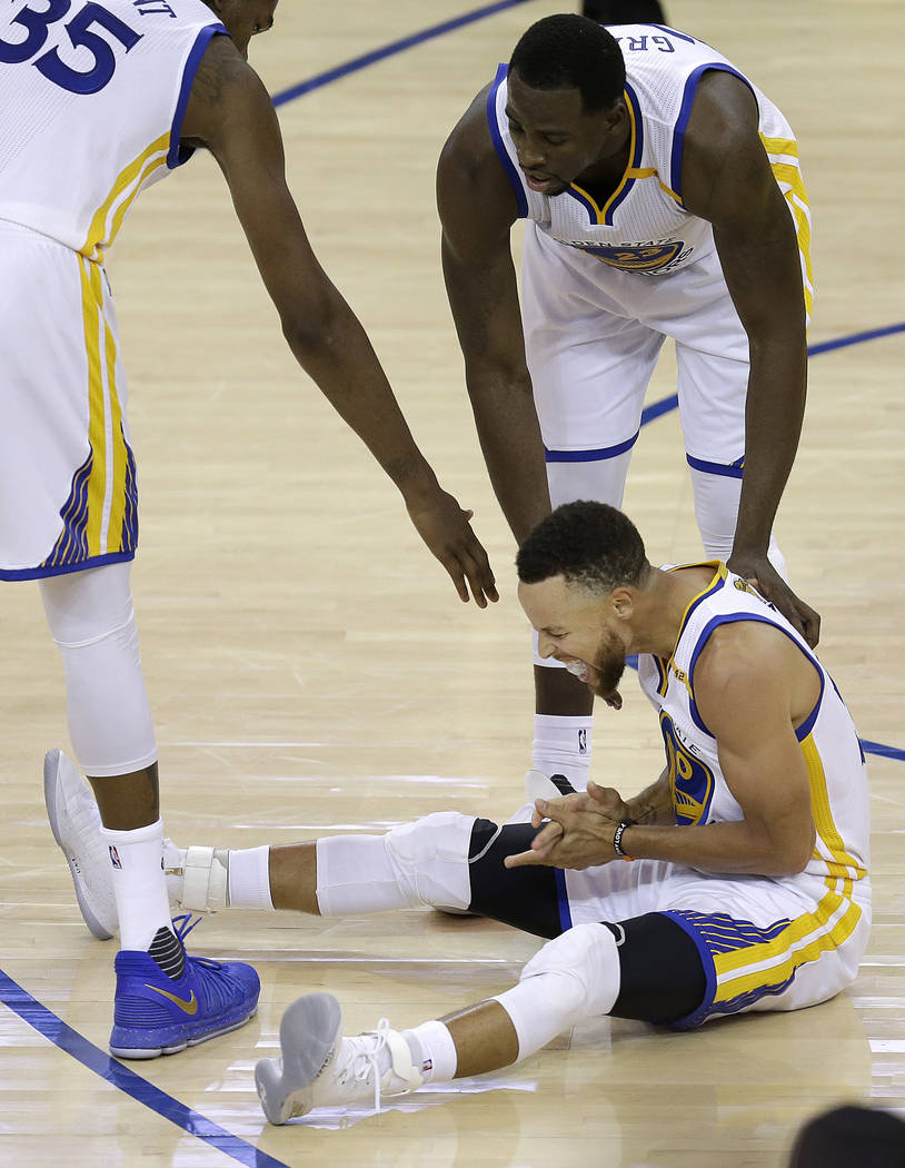Golden State Warriors guard Stephen Curry, bottom, reacts under forward Kevin Durant (35) and forward Draymond Green during the second half of Game 5 of basketball's NBA Finals against the Clevela ...