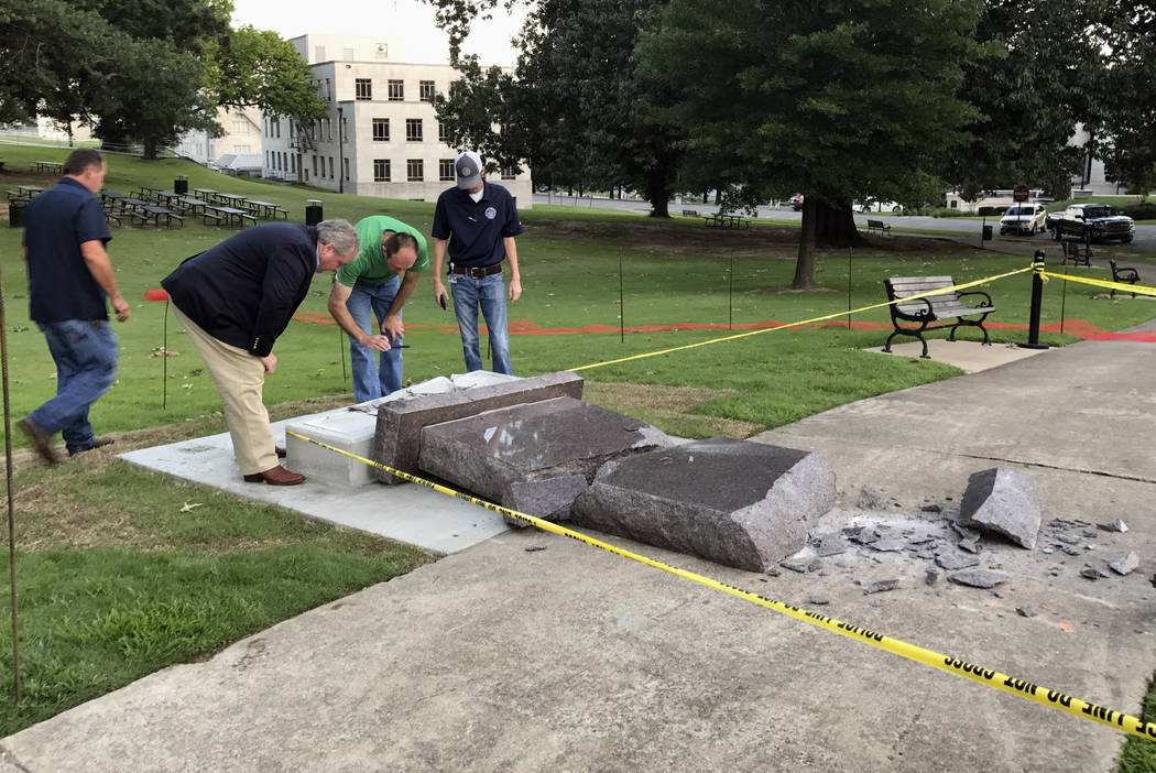 Personnel from the Secretary of State's office inspect the damage to the new Ten Commandments monument outside the state Capitol in Little Rock, Ark., Wednesday morning, June 28, 2017, after someo ...