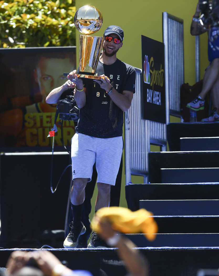 Golden State Warriors' Stephen Curry with the Larry O'Brien trophy during the Golden State Warrior's victory parade and rally in downtown Oakland, Calif. on Thursday, June 15, 2017. Chase Stevens  ...