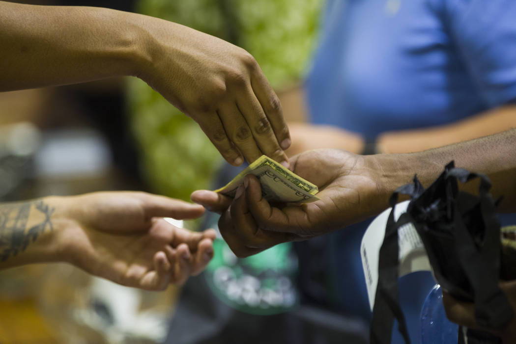 A customer receives change for a marijuana purchase as recreational sales become legal in Nevada at Reef Dispensaries in Las Vegas on Saturday, July 1, 2017. Chase Stevens Las Vegas Review-Journal ...