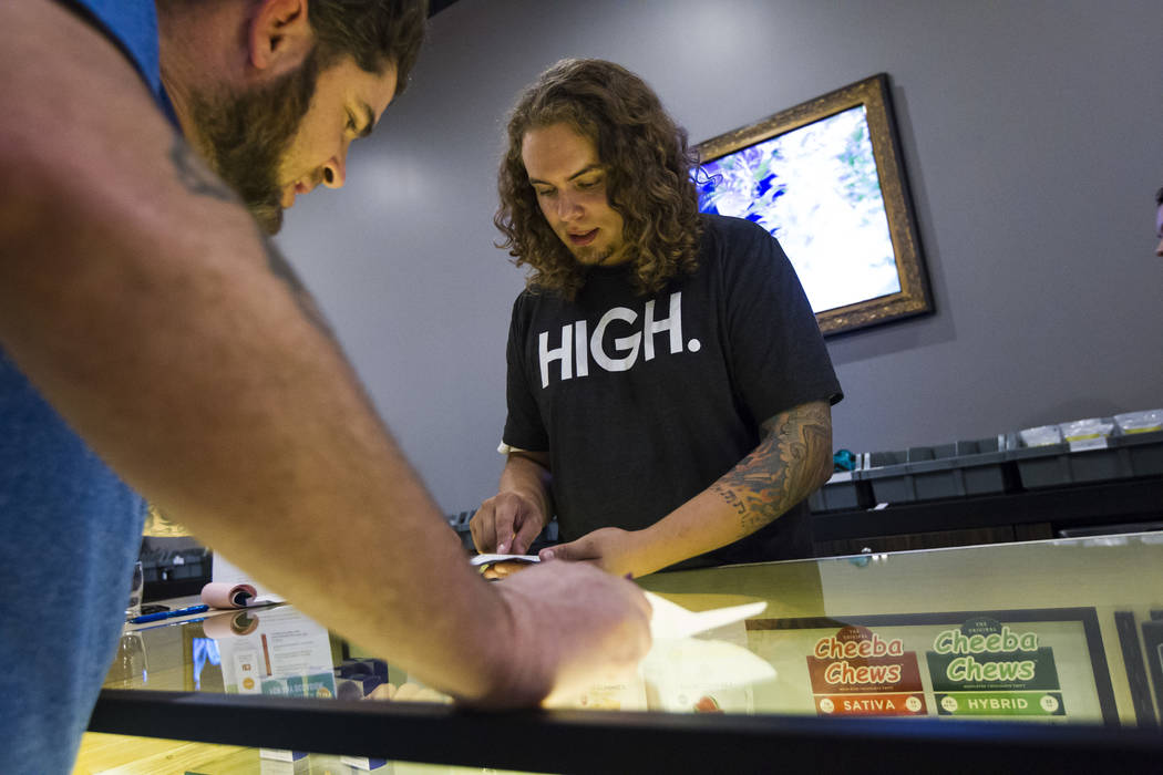 Budtender Tom Nieves, right, assists customer Ethan, of Henderson, during the first day of recreational marijuana sales at Acres Cannabis in Las Vegas on Saturday, July 1, 2017. Chase Stevens Las  ...