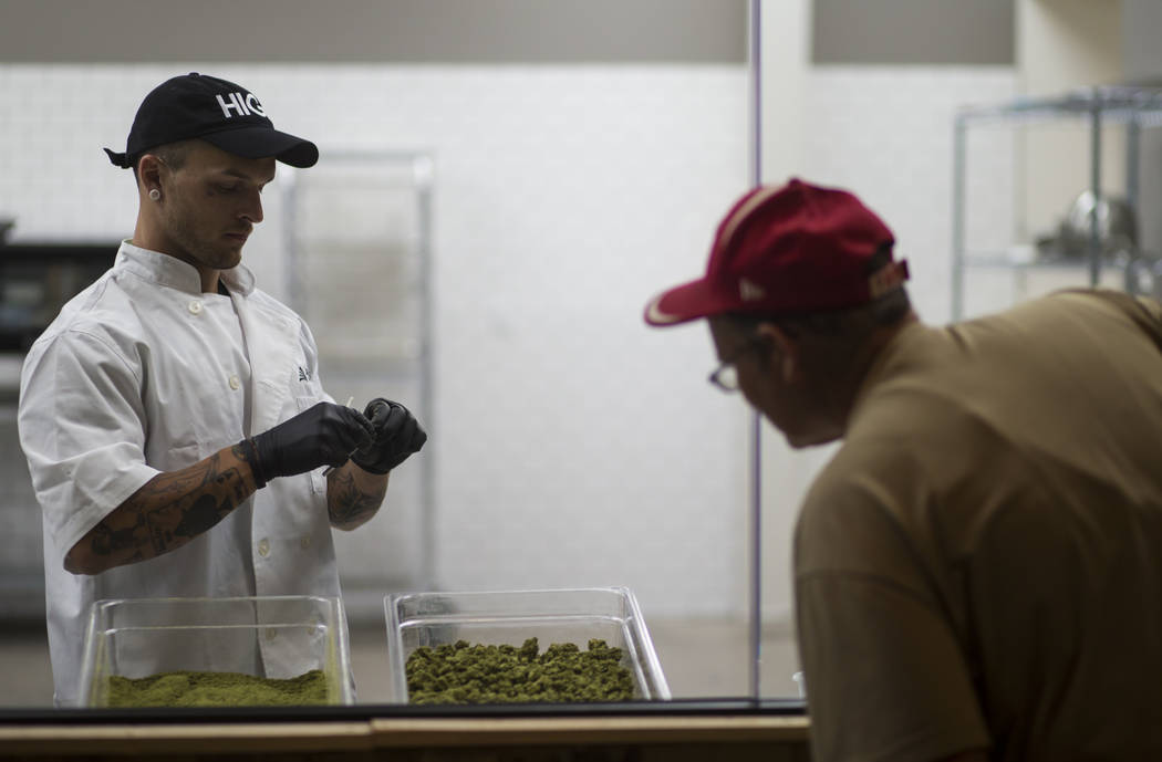 Anthony Hubbard, left, prepares rolled joints in the kitchen area at Acres Cannabis during the first day of recreational sales in Las Vegas on Saturday, July 1, 2017. Chase Stevens Las Vegas Revie ...